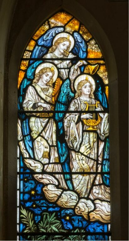 Stained glass window at St. Cynhaearn's depicting angels making the music of the heavens, by Powell & Sons